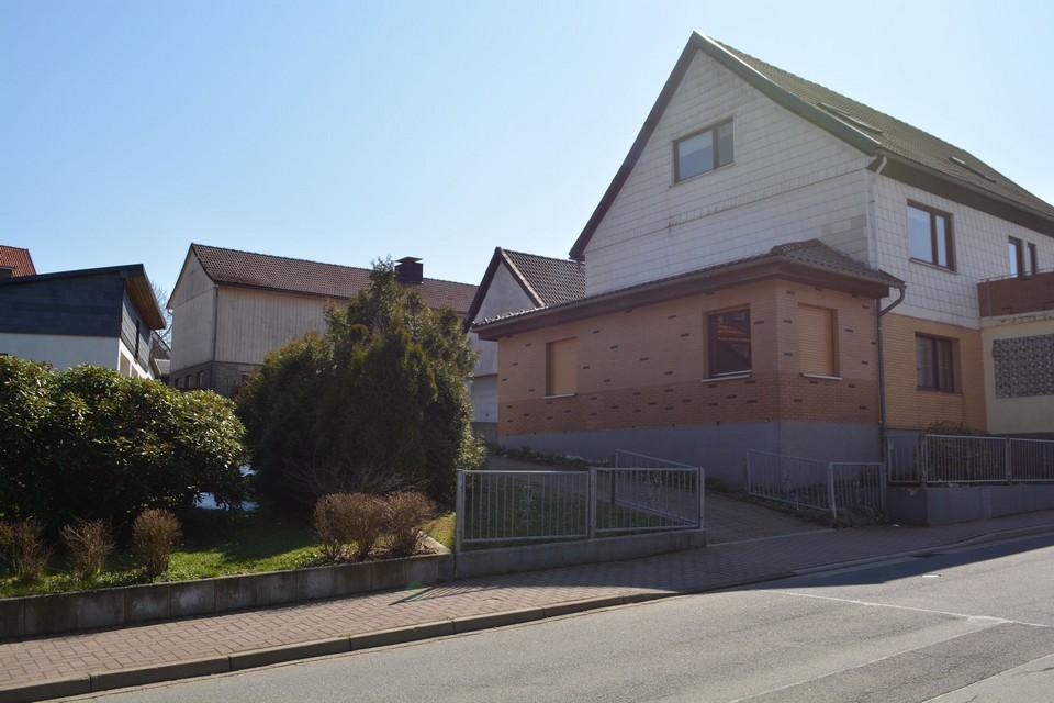 Многоквартирный дом с 5 гаражами, уютным участком и небольшой садовой хижиной.